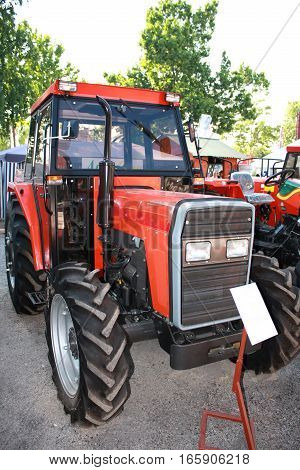 new and red tractor isolated on fair