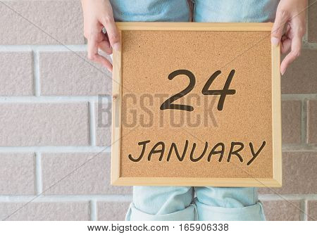 Closeup calendar at the cork board in hand of asian woman in front of her legs with 24 january word on brick wall textured background