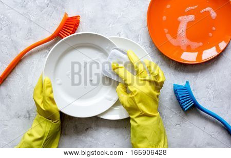 concept of woman washing dishes on gray background top view with hands