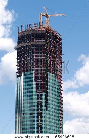 Yellow hoisting tower crane over construction building top