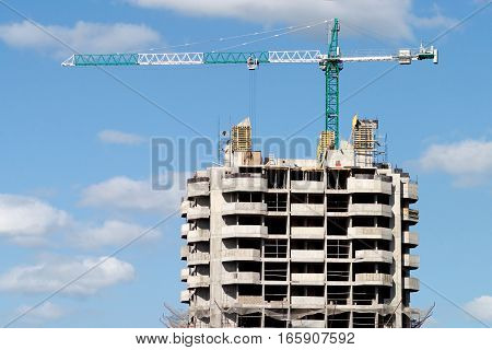 Big hoisting tower crane and top of construction building