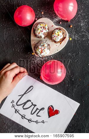 concept of Valentine's Day cupcakes on dark background top view.