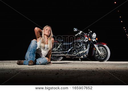 Young sexy blonde is sitting near her motorcycle