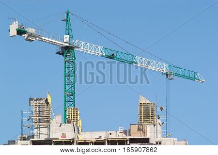 Big hoisting tower crane over construction building top isolated on blue