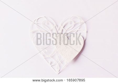 two paper lace hearts on a light background, warm tone, soft focus