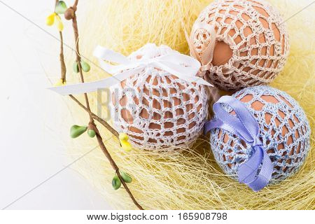 Three easter eggs in knitted bags in homemade yellow nest with spring decor on white background. Selective focus.