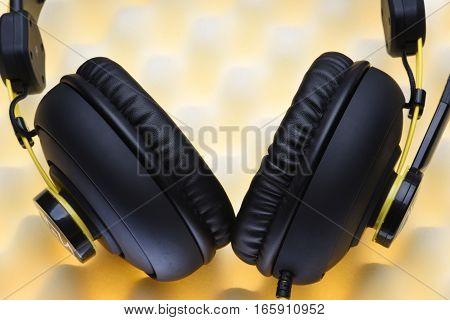 Headphones on acoustic foam in audio studio close up