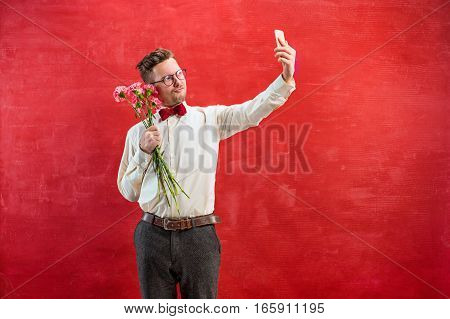 Young beautiful man with flowers and phone making selfie on red studio background