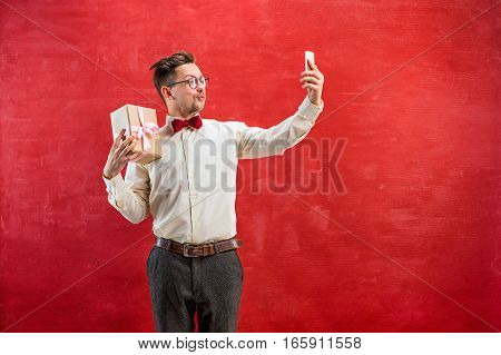 Young beautiful man with gift and phone making selfie on red studio background