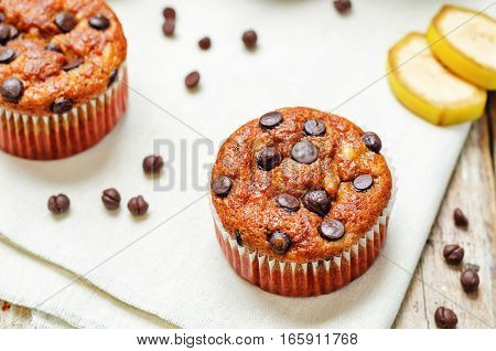 chocolate chips banana muffins on wood background