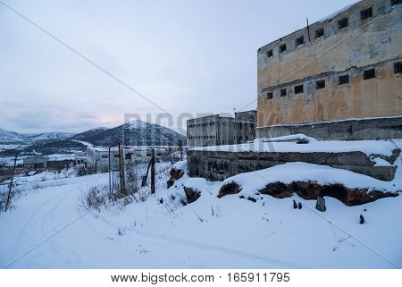Exterior of old decayed abandoned prison in Kolyma in evening light poster