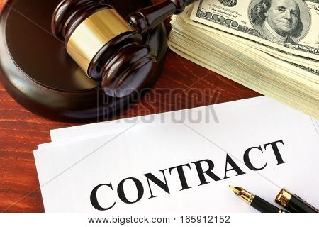 Contract, cash and gavel on a wooden surface.