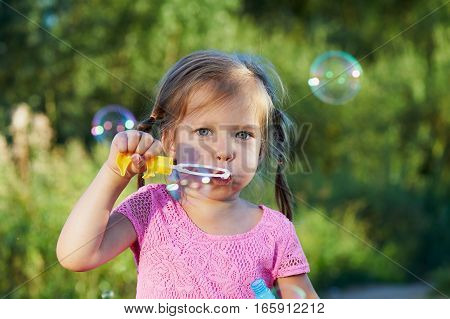 The girl in the pink dress 3 years and two braids enjoys life, inflating bubbles.