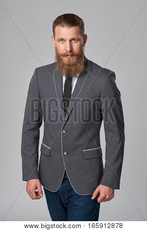 Hipster business man with beard and mustashes in suit standing over grey background