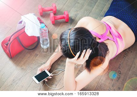Female fitness excercise concept with copy space Female listening music from smartphone aafter workout