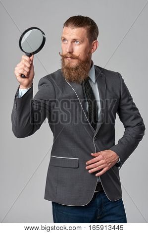 Serious hipster business man with beard and mustashes in suit looking up through magnifying glass, over grey background