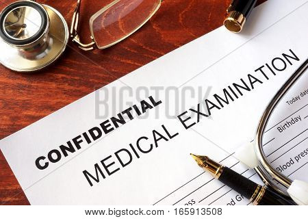 Medical examination form with title confidential on a table.