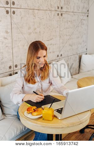 Young woman designing on a laptop in a cafe