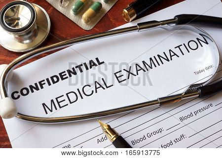 Medical confidentiality concept. Medical examination form on a table.