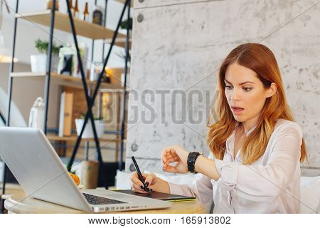 Young businesswoman looking at his watch at cafe