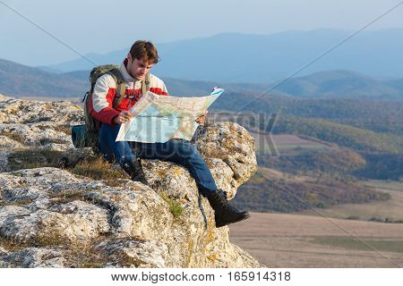 Backpacker Hiker Mountaineer On Cliff Edge Reading Map