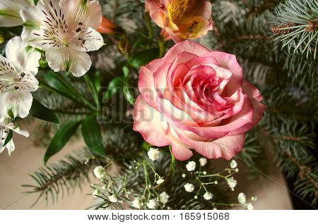 Bouquet of Alstroemerias  with  yellow-pink rose  and silver fir twigs on light wooden table