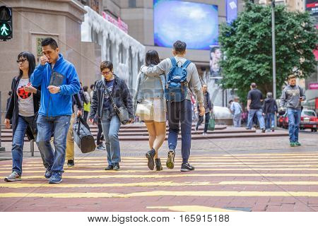 Hong Kong, China - December 6, 2016: Causeway Bay is one of the most attractive areas for tourists and business people and good for shopping. Asian happy couple crossing the Times Square intersection.