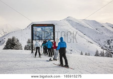 Mont Joux France- December 292014: Skiers looking to the slopes status board at the top of Mont Joux in Beaufortain Massif in Haute-Savoie close to Mont Blanc Massif. In the distance can be seen Mont Joly (2525m).