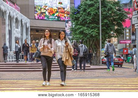 Hong Kong, China - December 6, 2016: asian couple of friends women walking happy outside the mall of Times Square, in luxury shopping district Causeway Bay.