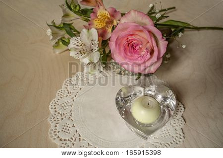 Bouquet of  yellow-pink rose  with Alstroemerias, crystal candlestick with patterned napkin on  wooden table