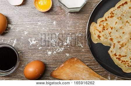 Thin pancake in frying pan on wooden table with flour and eggs