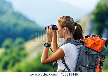 Hiker Looking In Binoculars Enjoying Spectacular View On Mountain Top Above The Clouds