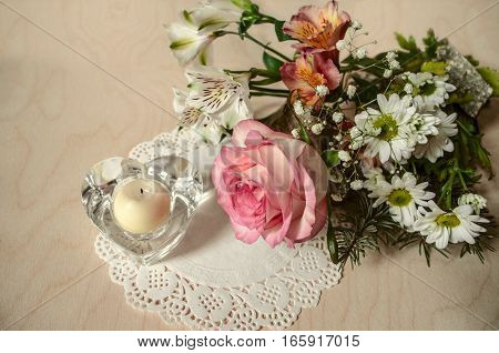 Bouquet of delicate flowers with pink rose and crystal candlestick heart on paper patterned napkin