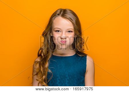 The face of playful happy teen girl with long hair on orange studio background