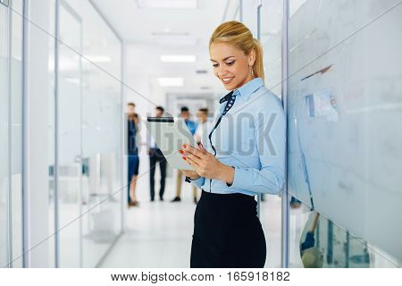 Business Woman standing in hall and using digital tablet