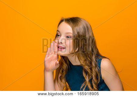 The face of playful happy teen girl saying something on orange studio background