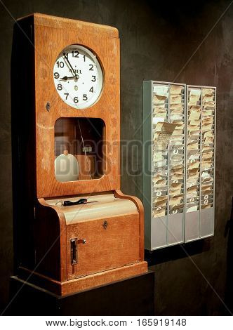 BERLIN GERMANY - 29 JANUARY 2005: A retro time clock with a rack of punch cards used to determine the hours worked by employees.