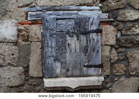 Old wooden shutters with iron hinges on stone wall background in medieval village (commune) near Lyon. Paruzhes, France