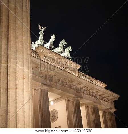 A night view of the Brandenburg Gate Berlin with focus on the familiar quadriga atop the monument.