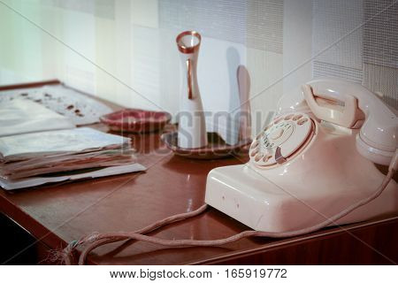 An retro scene of an old 1950's telephone in a contemporary setting with phone book on a side table.