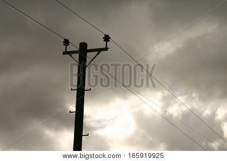 UK telegraph pole silhouetted against dark ominous storm clouds.