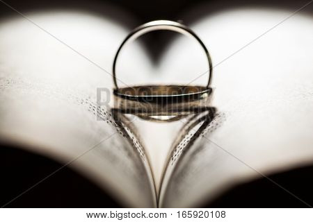 Wedding rings inter placed to create two heart shaped shadows (a unique placement)