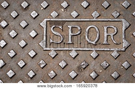 A manhole drain cover in Rome Italy with the letters SPQR.