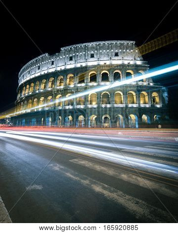 A long-exposure night view of the Colosseum in Rome Italy with traffic illumination streaming by.
