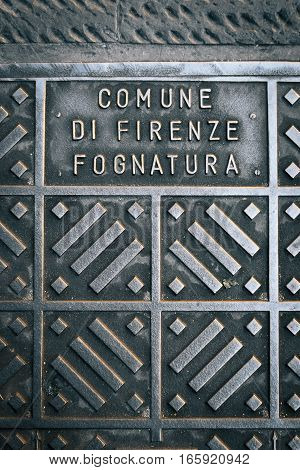 Detail from a manhole cover in the Italian town of Firenze (Florence). 'Comune di Firenze Fognatura' translates to 'Town of Florence Sewer'.