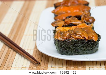 Sushi Japanese food on white plate with chopsticks