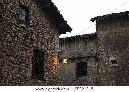 Burning lantern medieval. Evening. Stone houses with a tiled roof in the medieval village (commune) near Lyon. The place where the historic shoot movies in December 20, 2016, Paruzhes, France