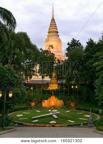 Asian temple Wat Phnomin Phnom Penh Cambodia at cloudy sunset slightly illuminated