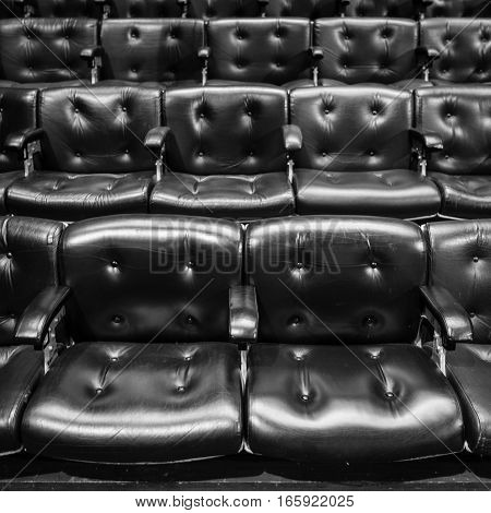Full frame detail from rows of raked leather seating of the type found in conference or concert halls.