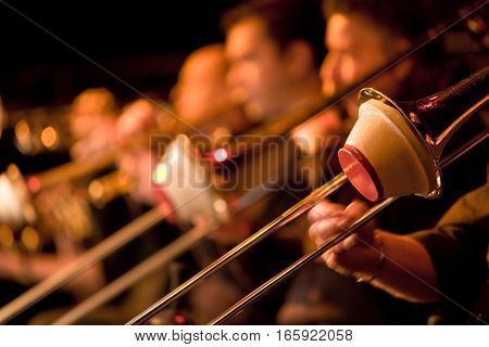 Shallow focus on the foreground trombonist with the rest of the section falling into background blur. Big band brass section with cup mutes.